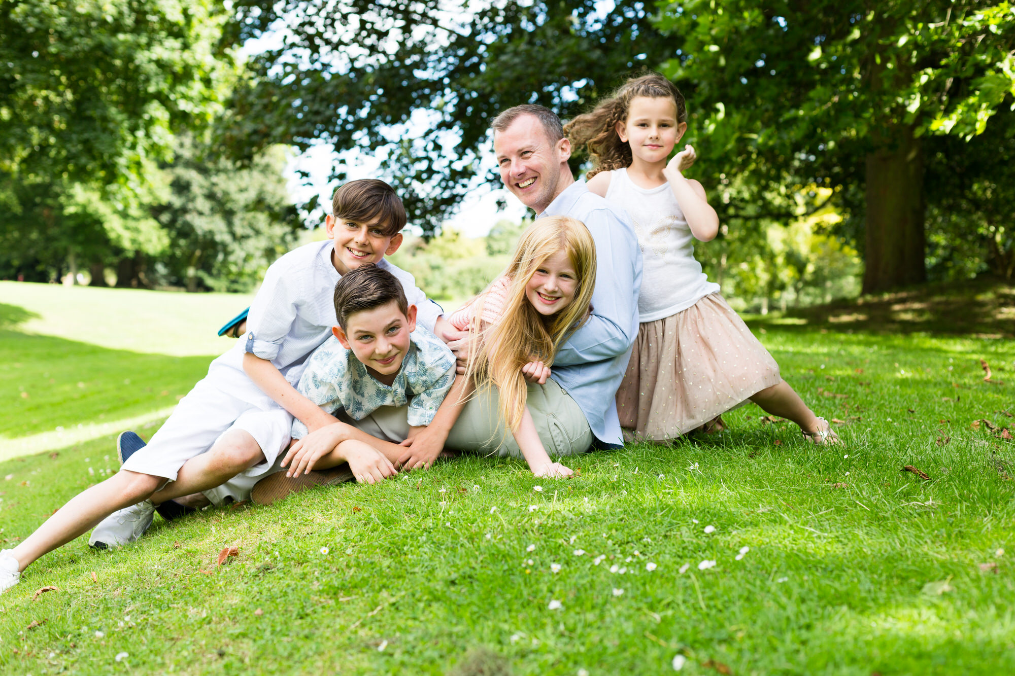 family laying on grass bank laughing and having fun at their family photoshoot in Bexley