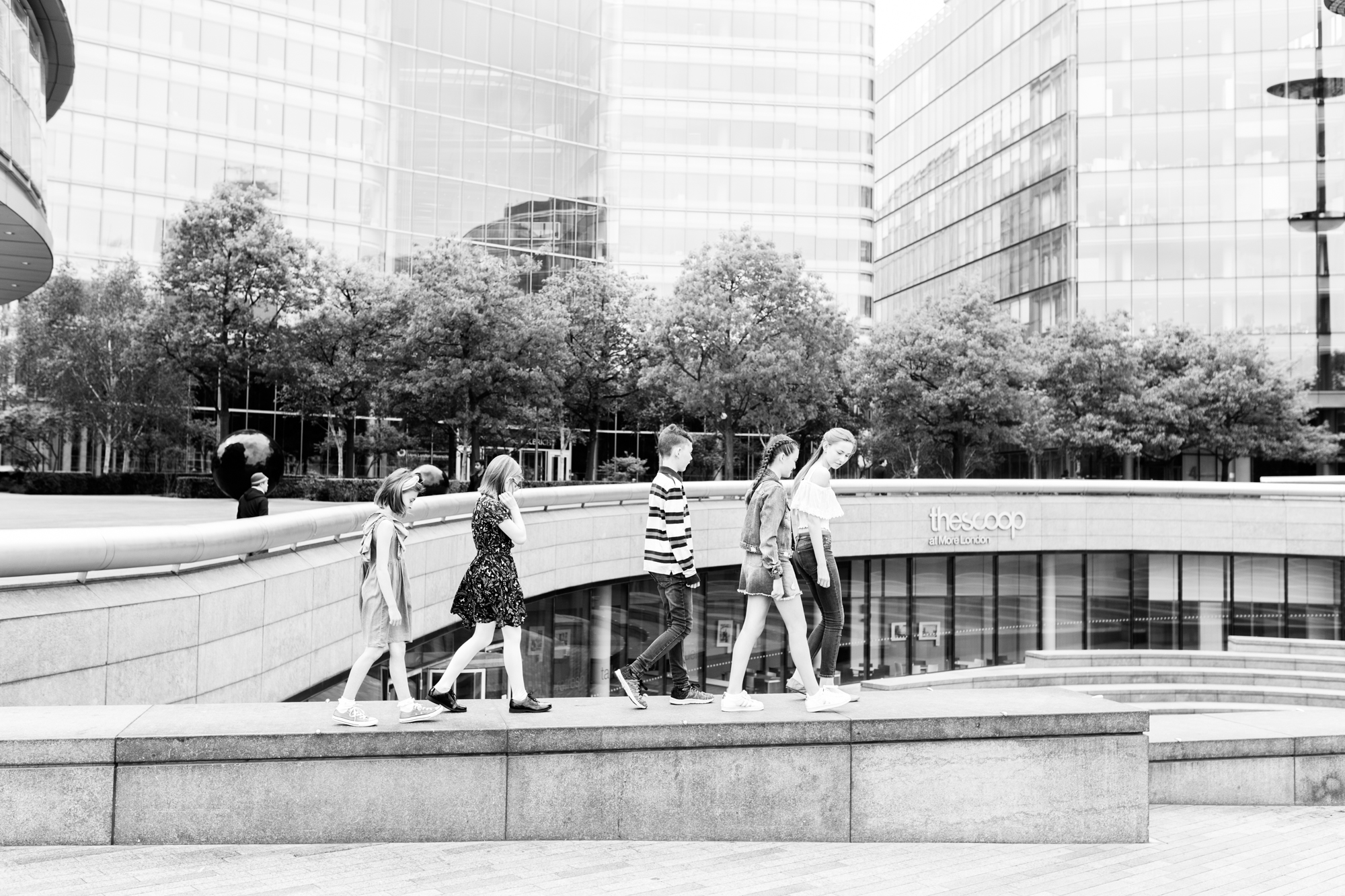 children walking along a raised platform at their extended family photoshoot in London