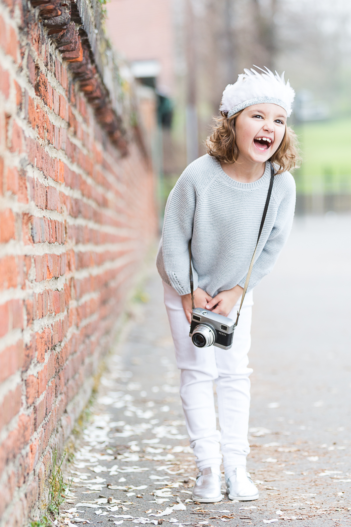 little girl laughing at the camera with a vintage camera and feather crown at her family photoshoot at Hall place Bexley