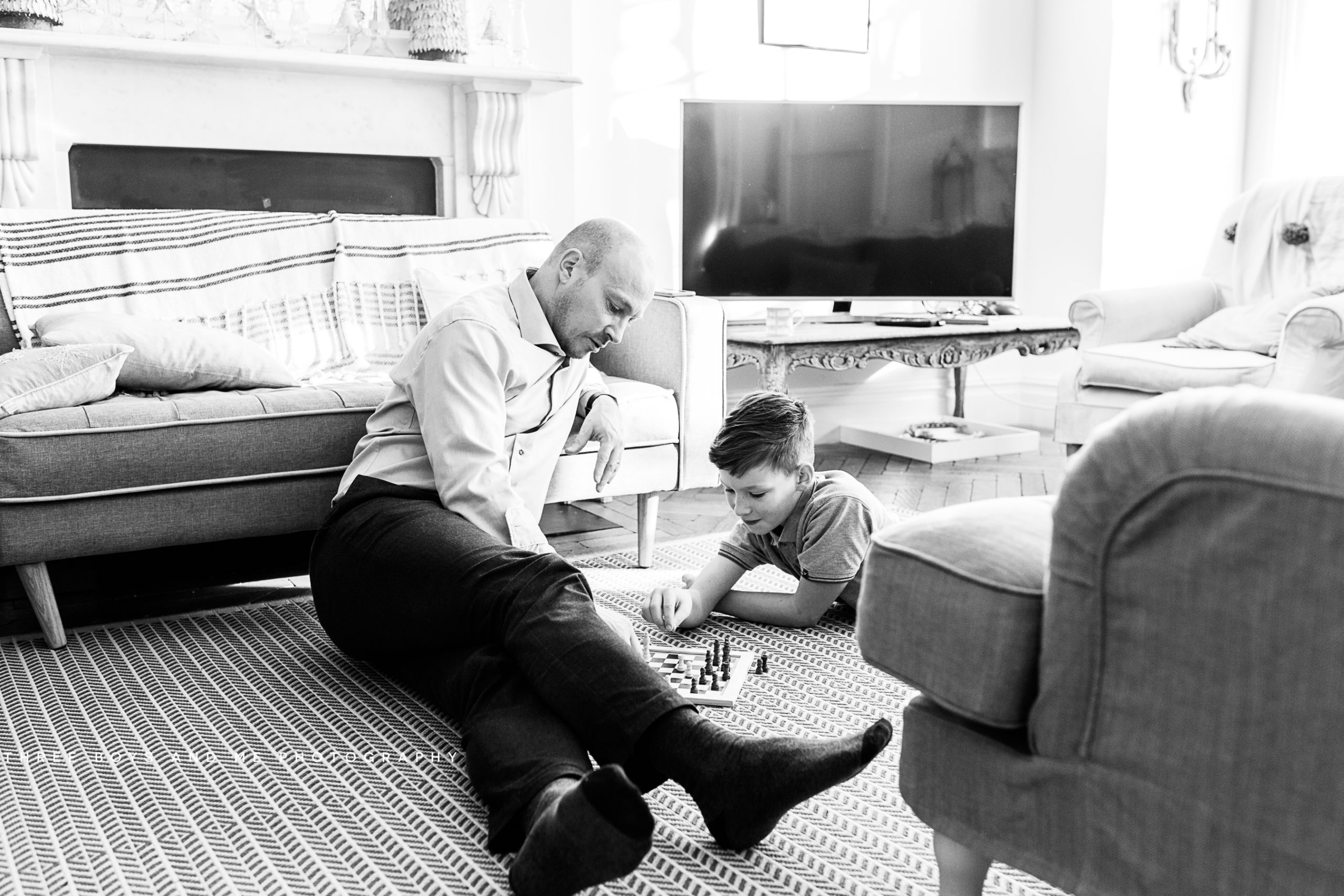 dad and son playing chess during their documentary family photoshoot in london