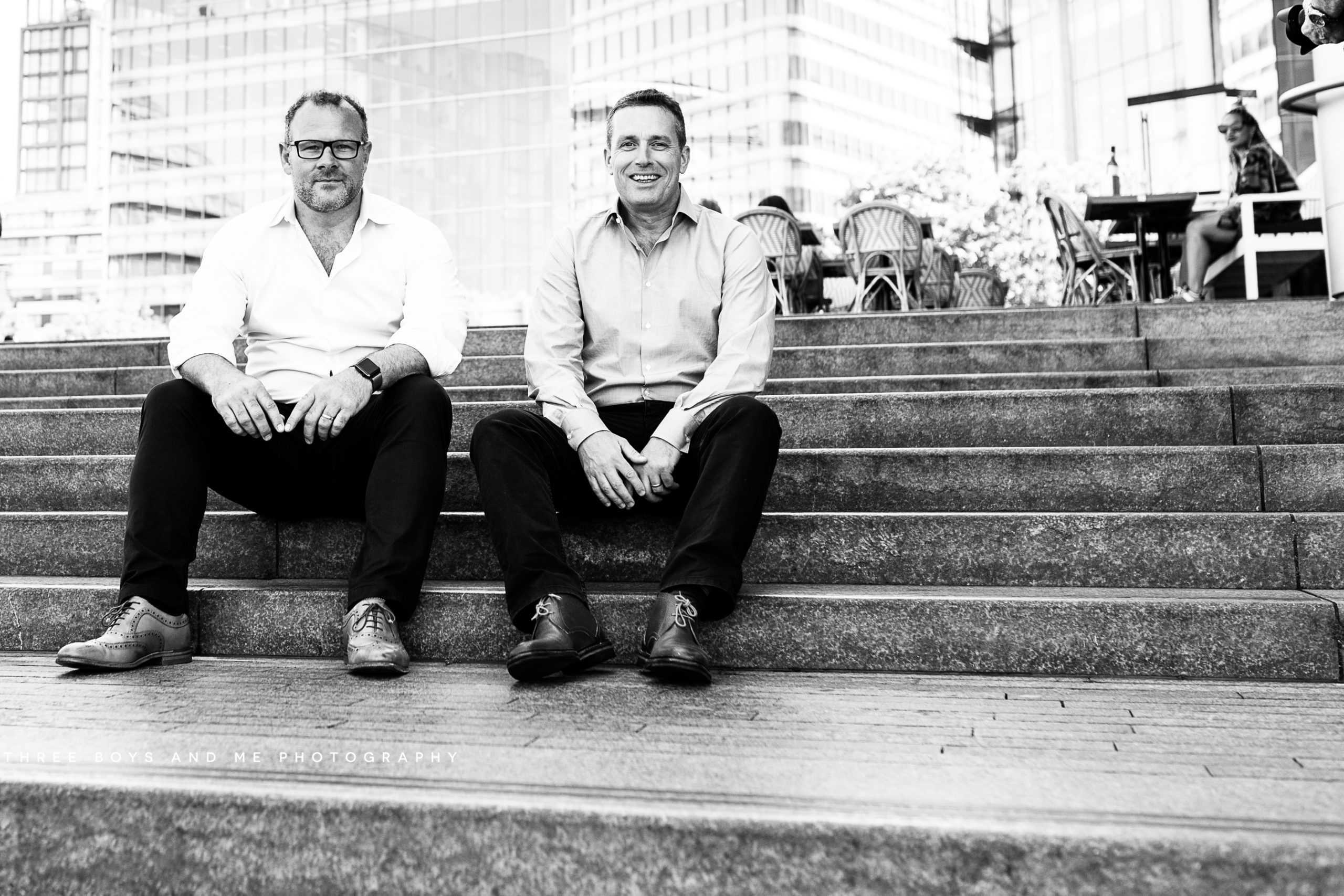 company directors sitting on stone steps at London Bridge having a chat on their commercial meet the team photoshoot