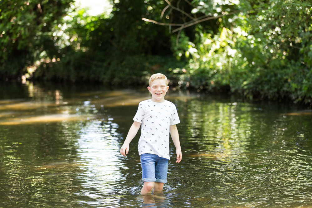young boy paddles in stream in shoreham at their Kent family photoshoot