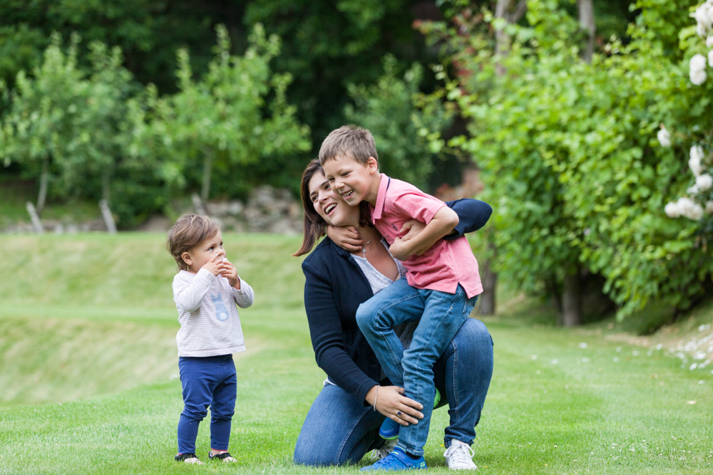 mum and children play on the grass at Riverhill Himalayan Gardens at their documentary family photoshoot in Kent