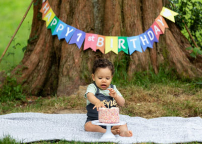 beautiful little boy playing with his cake at his outdoor cake smash in Bexley