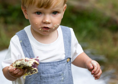 little boy eating cake at his Bexley outdoor cake smash photoshoot