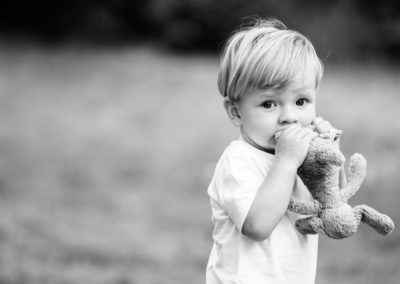 Beautiful black and white natural photograph of a baby boy with his favourite teddy