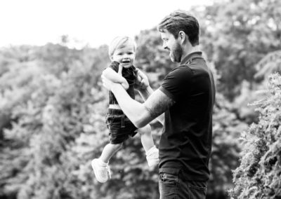 black and white candid image of little boy and dad at their Bexley family photoshoot