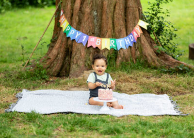 little boy covered in cake at his outdoor cakesmash photoshoot in Bexley