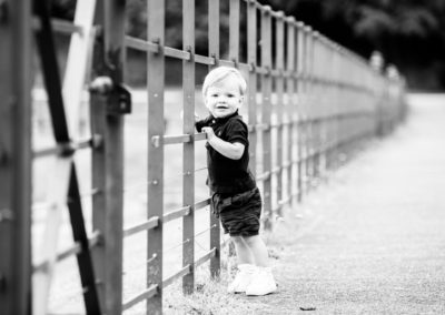 black and white image of little boy leaning on railings at his Bexley photoshoot