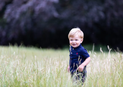 little boy smiling in grass at his Bexley family photoshoot