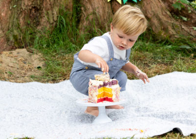 little boy at his outdoor cakesmash photoshoot with his Marks & Spencer rainbow cake in Bexley