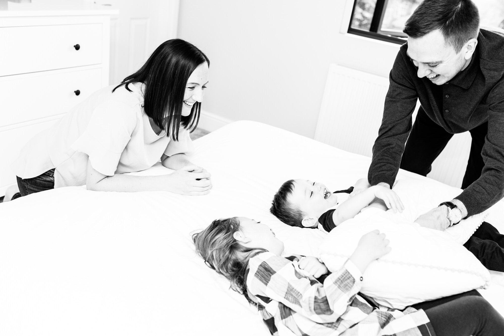 laughing children being tickled by dad with mum smiling at home documentary photoshoot in Bexley