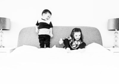 two siblings jumping on bed in a Bexley lifestyle at home photoshoot in black and white