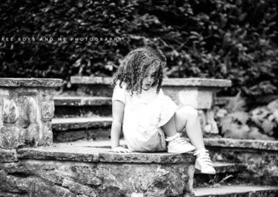 natural photograph of a Little girl looking down climbing on a low wall in Bexley