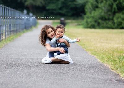 sister cuddling brother sat on the floor in the park smiling at their Bexley family photoshoot