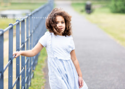 beautiful natural portrait of a stunning little girl leaning against the railings at her family photoshoot in Bexley