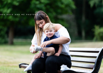 mum and toddler sitting on bench putting on babies shoe during their natural photoshoot in Bexley