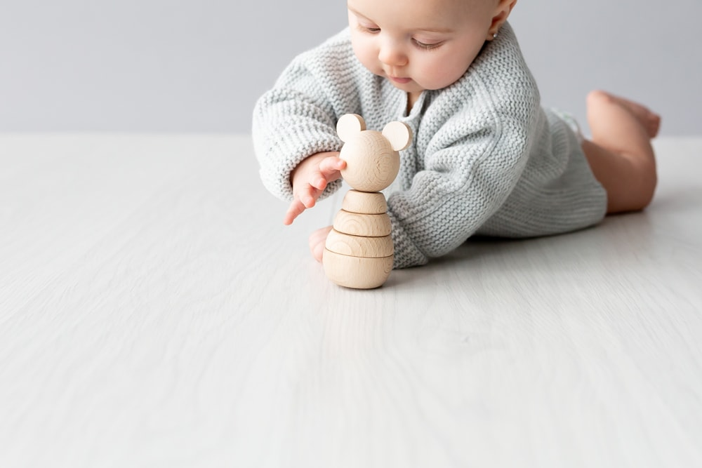 baby girl In grey jumper playing with wooden stacking mouse at Bexley studio sitter photoshoot
