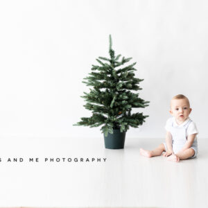 baby boy dressed in white with a green christmas tree at his bexley christmas studio photoshoot