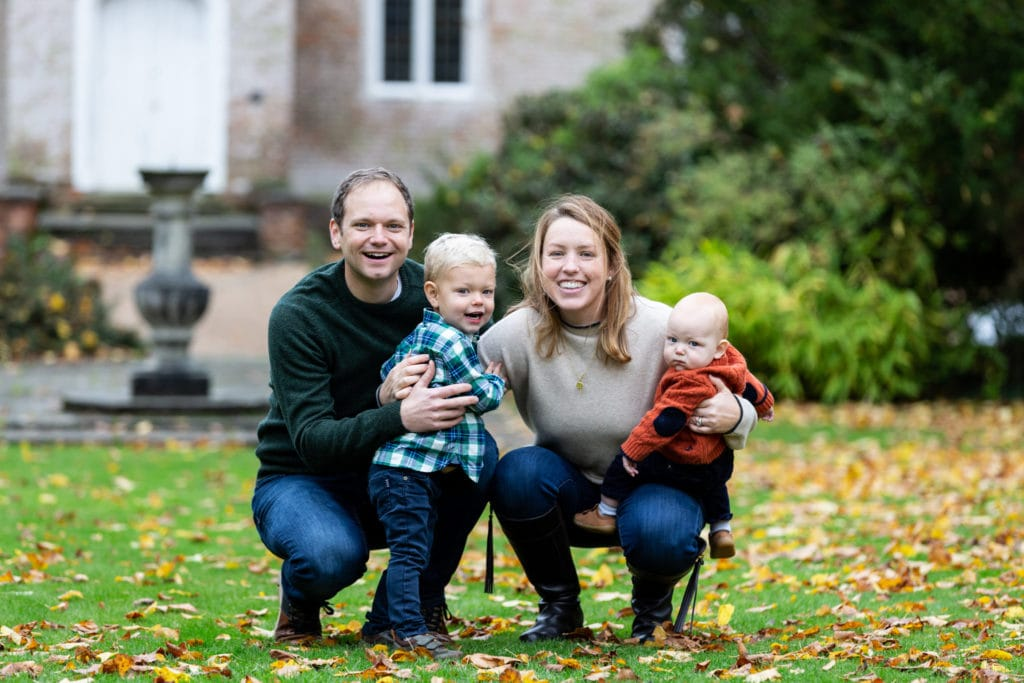 family of 4 with two little boys in front of an old house at their Sevenoaks family photoshoot