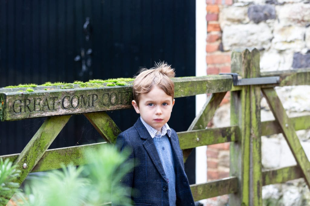 portrait shot of little boy leaning against a moss covered gate at his Sevenoaks family photoshoot