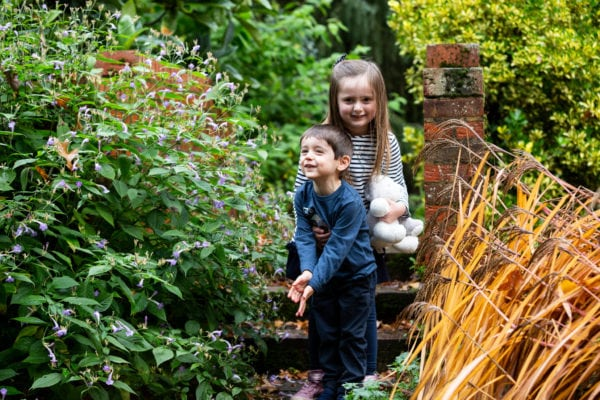 brother and sister laughing in the beautiful autumn colours at Great comp garden on their Sevenoaks family photoshoot
