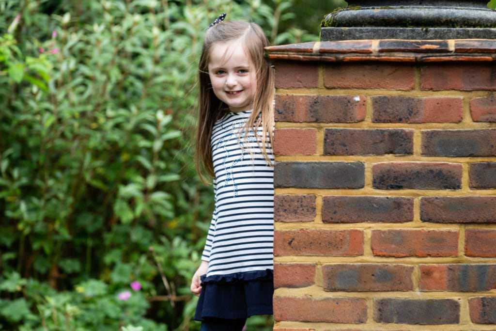 little girl looking round a brick pillar at her Sevenoaks family photoshoot