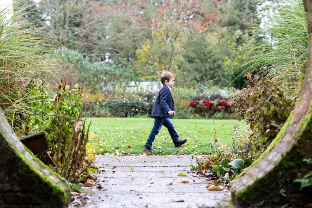 little boy walking through a circular hole in the wall like abbey road Beatles cover at his Sevenoaks family photoshoot