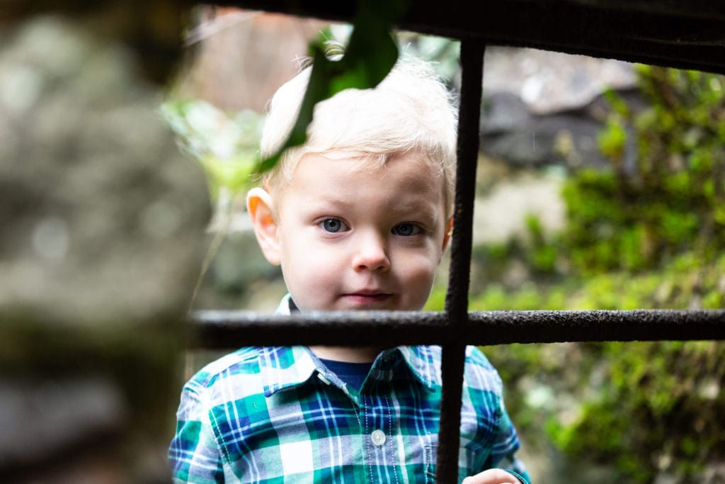 little boy looking through a rusty window frame at his Sevenoaks family photoshoot in Kent