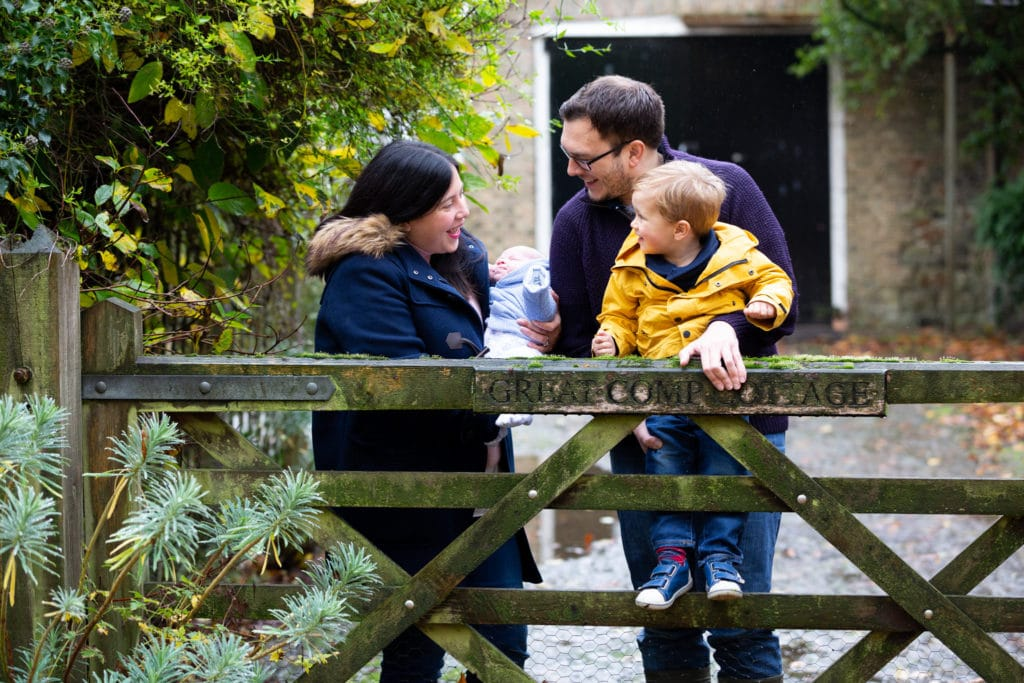 family of 4 with newborn baby smiling at each other at a gate during their Sevenoaks family autumn photoshoot
