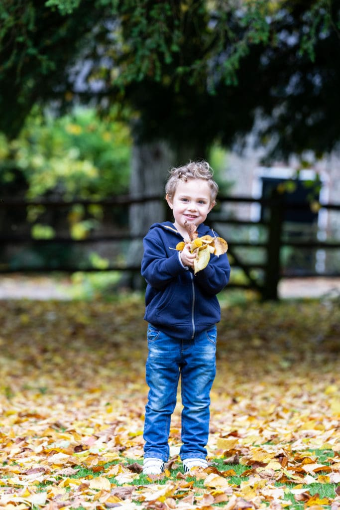 little boy holding a handful of autumn leaves and smiling at his Sevenoaks family photoshoot