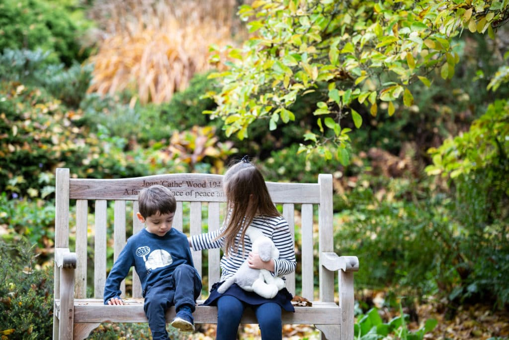 candid shot of brother and sister sat on a bench at their family photoshoot in Sevenoaks in Kent