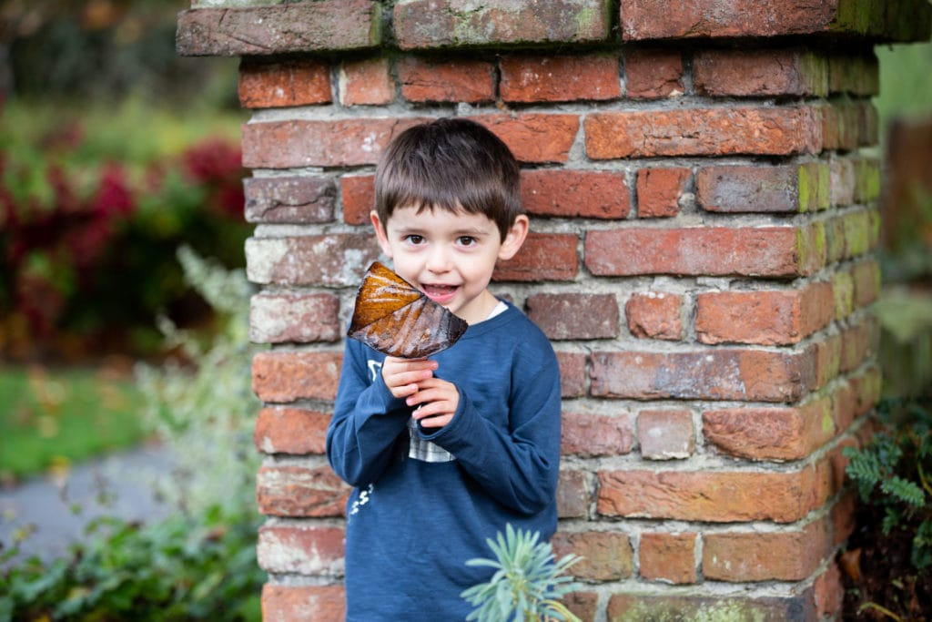 little boy holding a leaf and smiling against a brick wall at his autumn family photoshoot in Sevenoaks