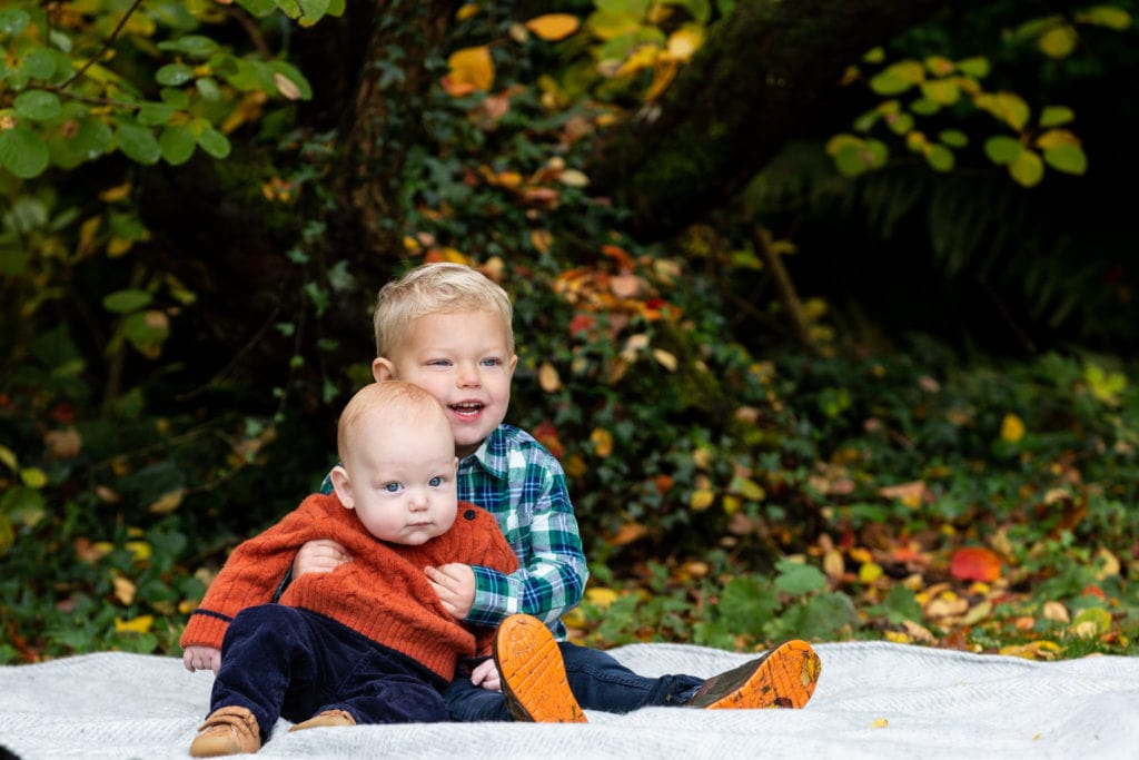 two little brothers sat on a blanket at their family autumn photoshoot at Great comp garden Sevenoaks