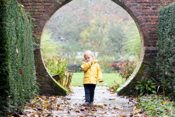 little boy in a yellow coat framed in a brick archway at his sevenoaks autumn photoshoot