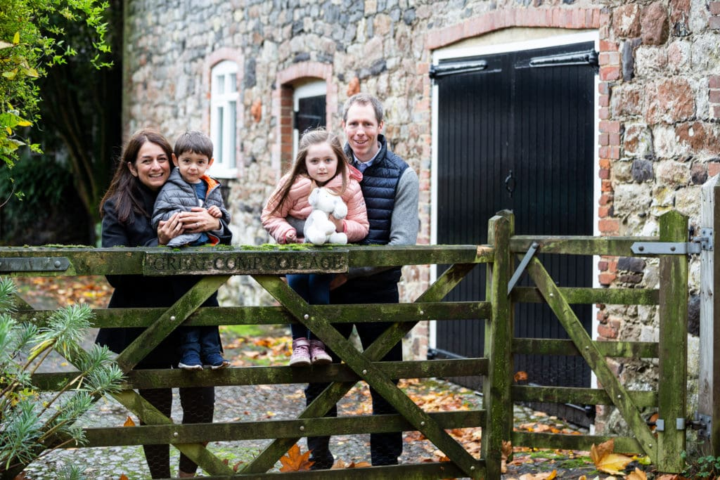 family standing by rustic old wooden gate at great comp gardens at their sevenoaks autumn photoshoot