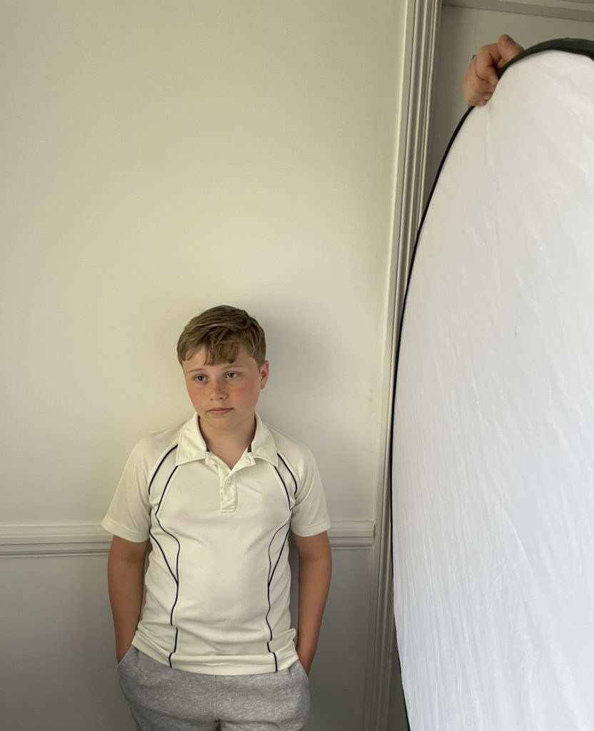 young child stands by wall demonstrating how use of reflector eliminates shadows on face