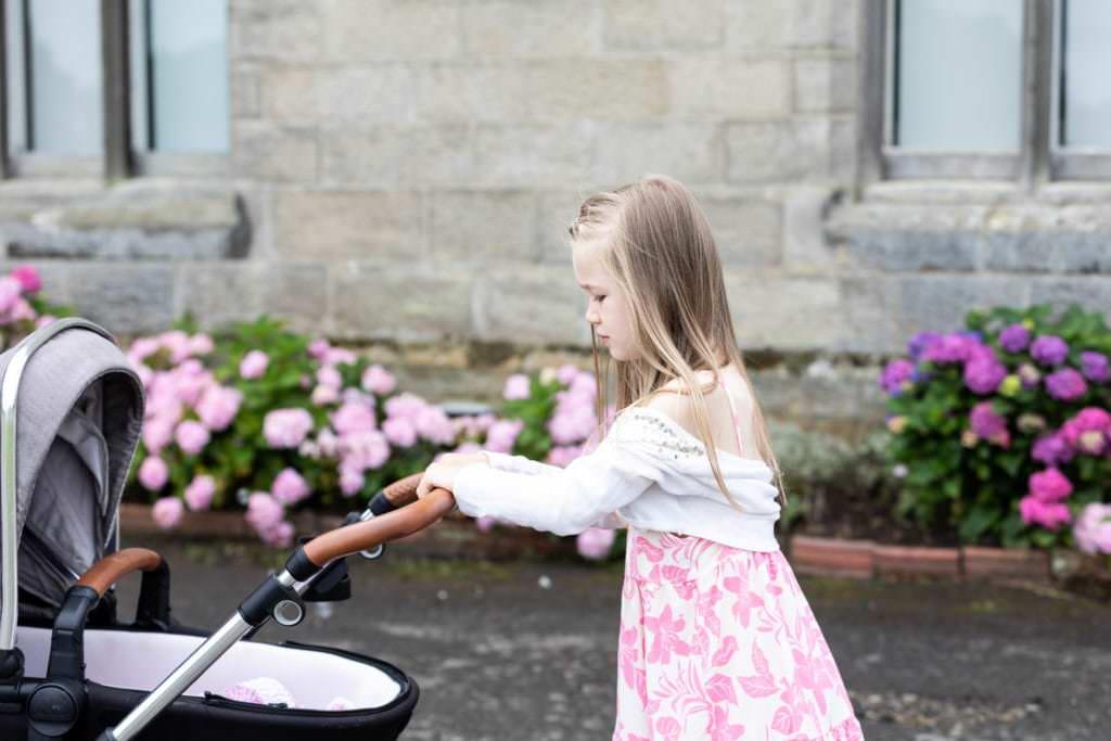 big sister pushing newborn sisters pram at her family photoshoot in sevenoaks