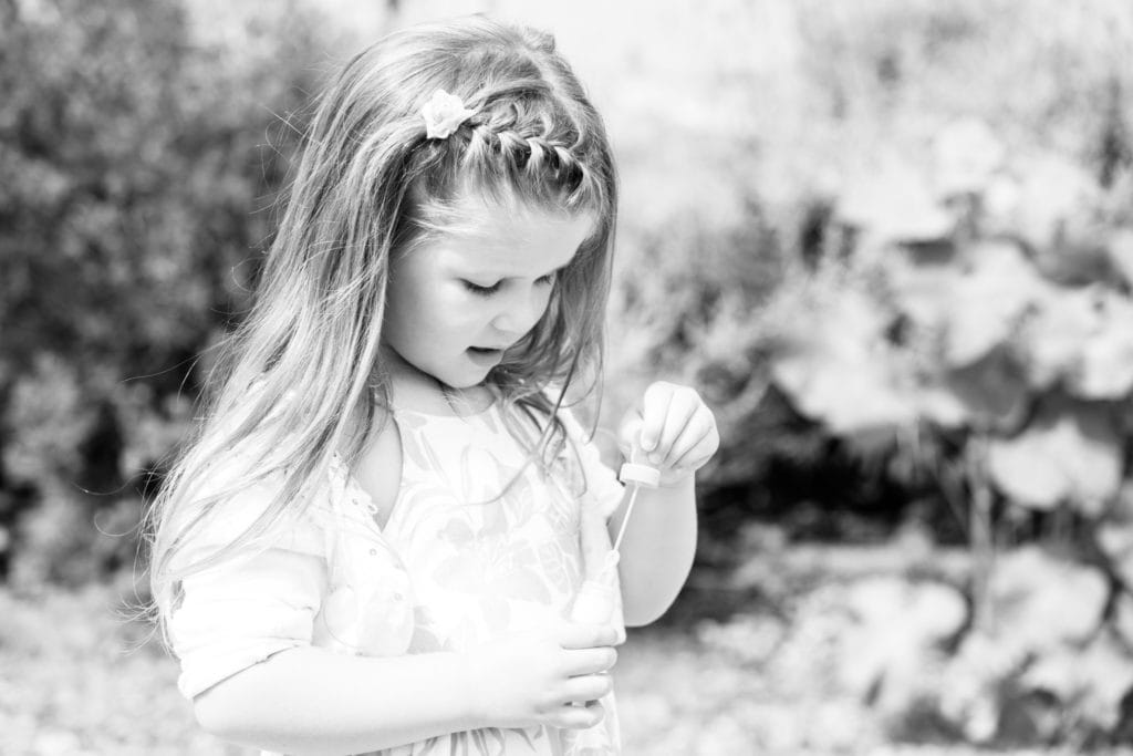 little girl playing with bubbles looking down at her family photoshoot in sevenoaks
