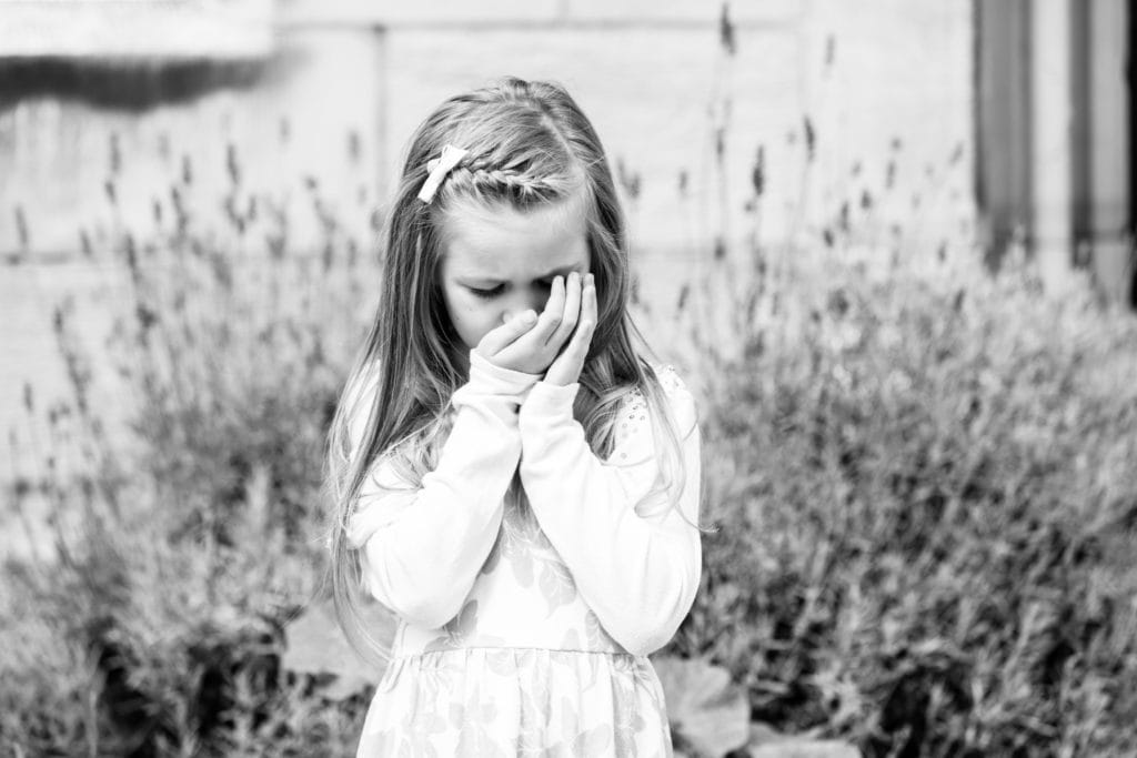 little girl smelling lavender in her hands at her family photoshoot in Sevenoaks