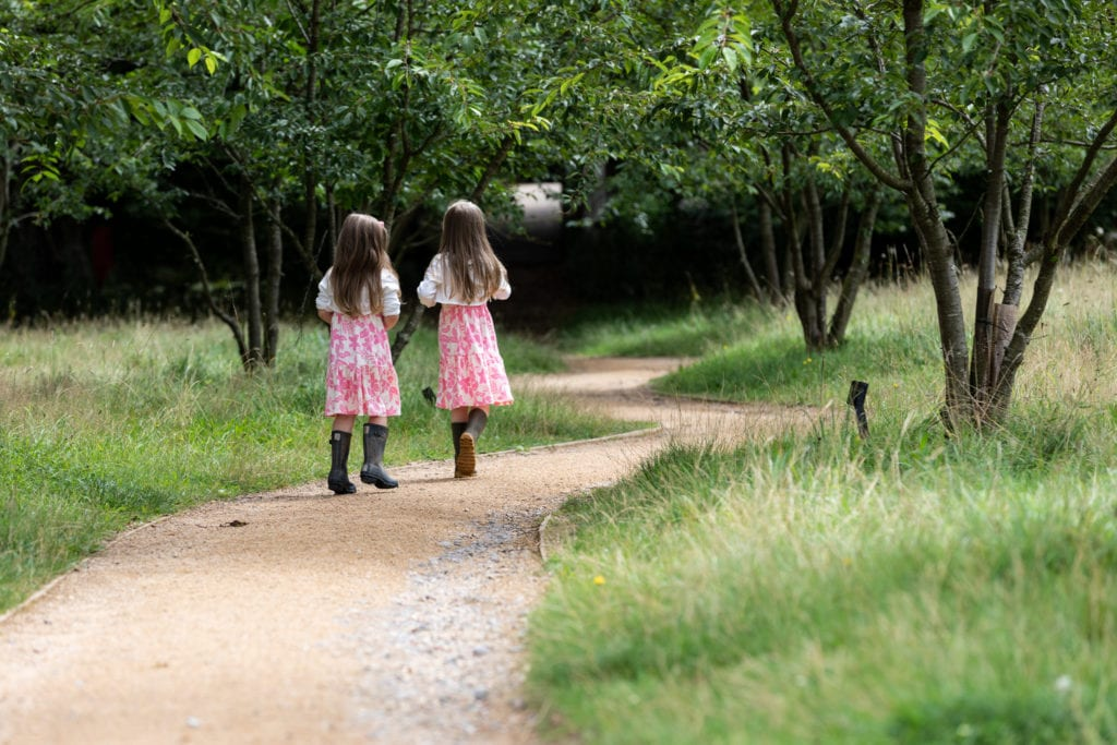 two sisters walk away from the camera in woodland at their sevenoask family photoshoot