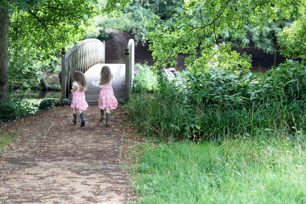 two sisters running towards a bridge at their sevenoaks family photoshoot