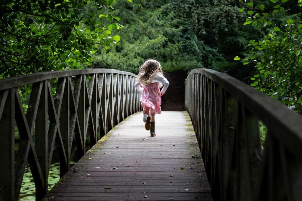 little girl running away from the camera across a bridge at her sevenoaks family photoshoot
