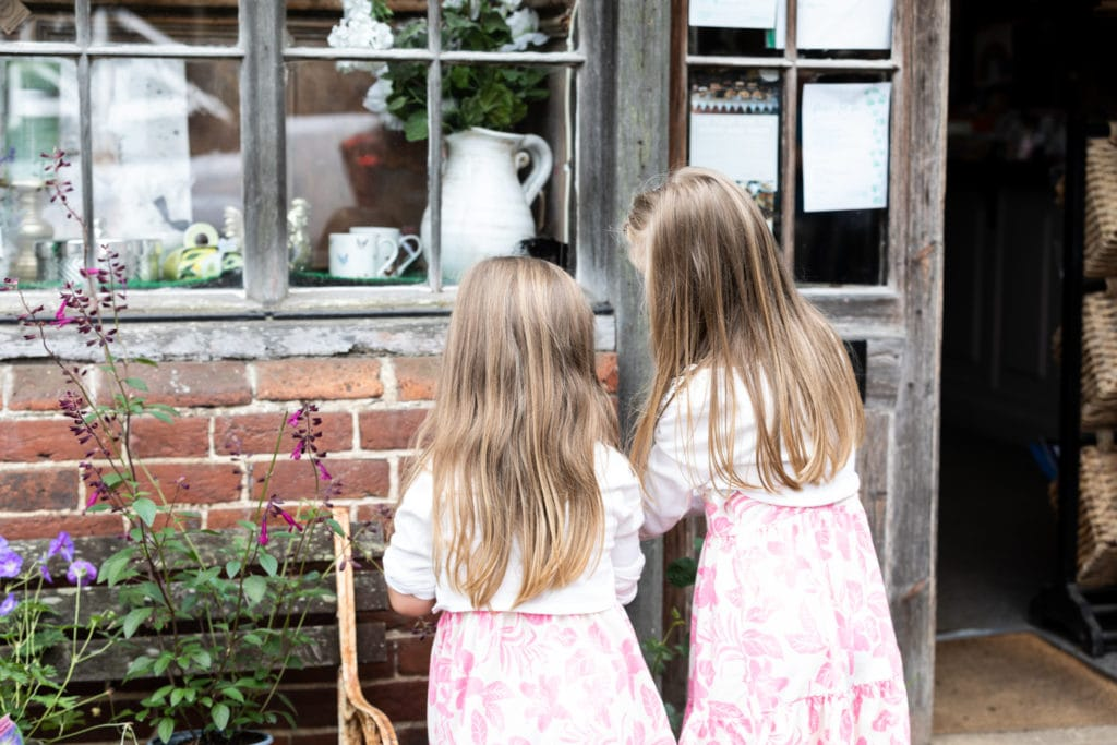 sisters looking in a corner shop window at their sevenoaks newborn family photoshoot