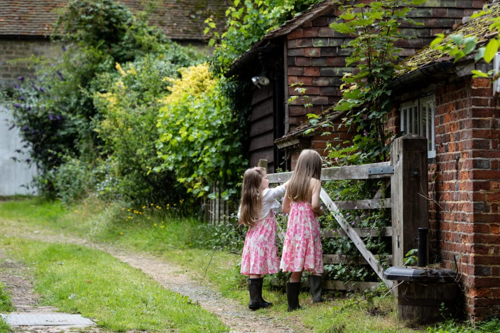sisters play by a wooden gate at their sevenoaks family newborn shoot