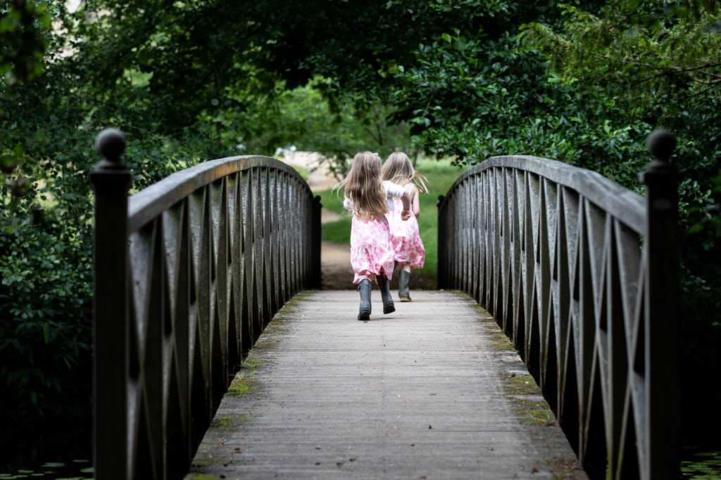 lilttle girls wearing dresses and wellies running across a bridge at their sevenoaks family photoshoot