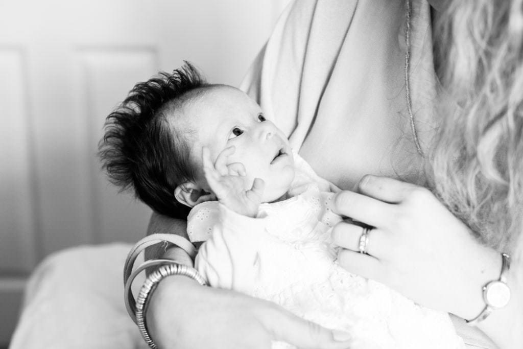 beautiful baby girl looks up at her mummy on a newborn family photoshoot in sevenoaks