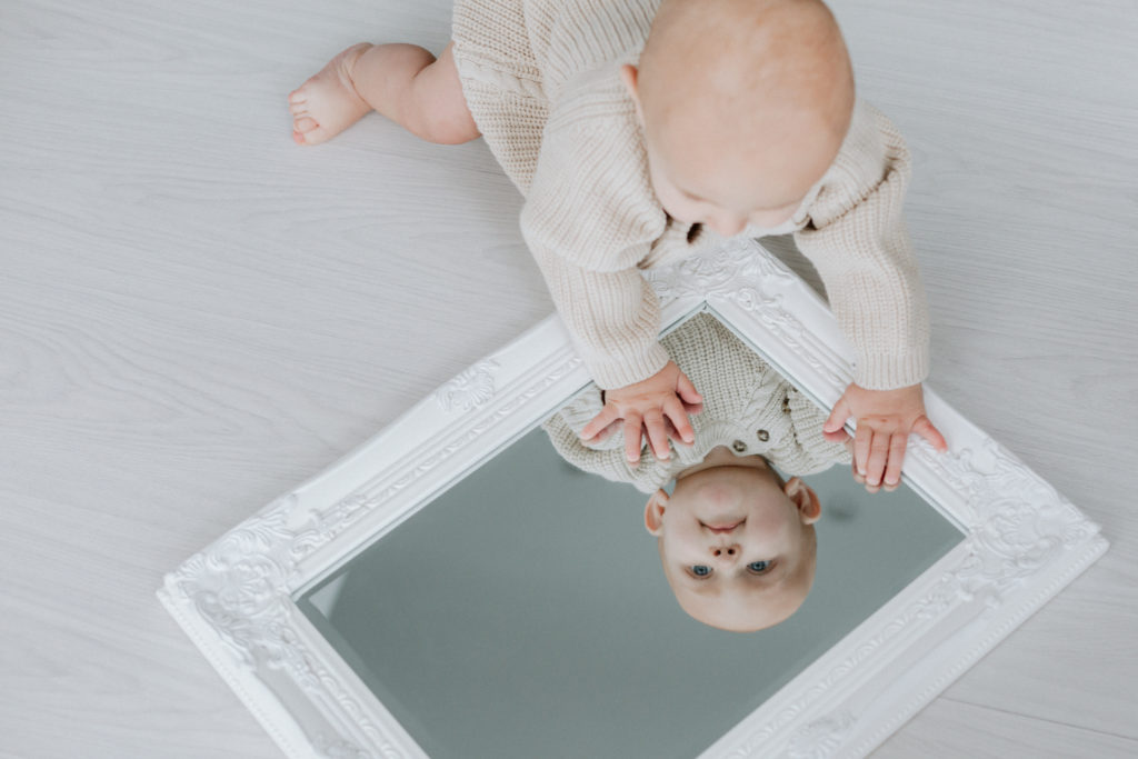 baby playing peek-a-boo in the mirror taken at his Bexley baby photoshoot