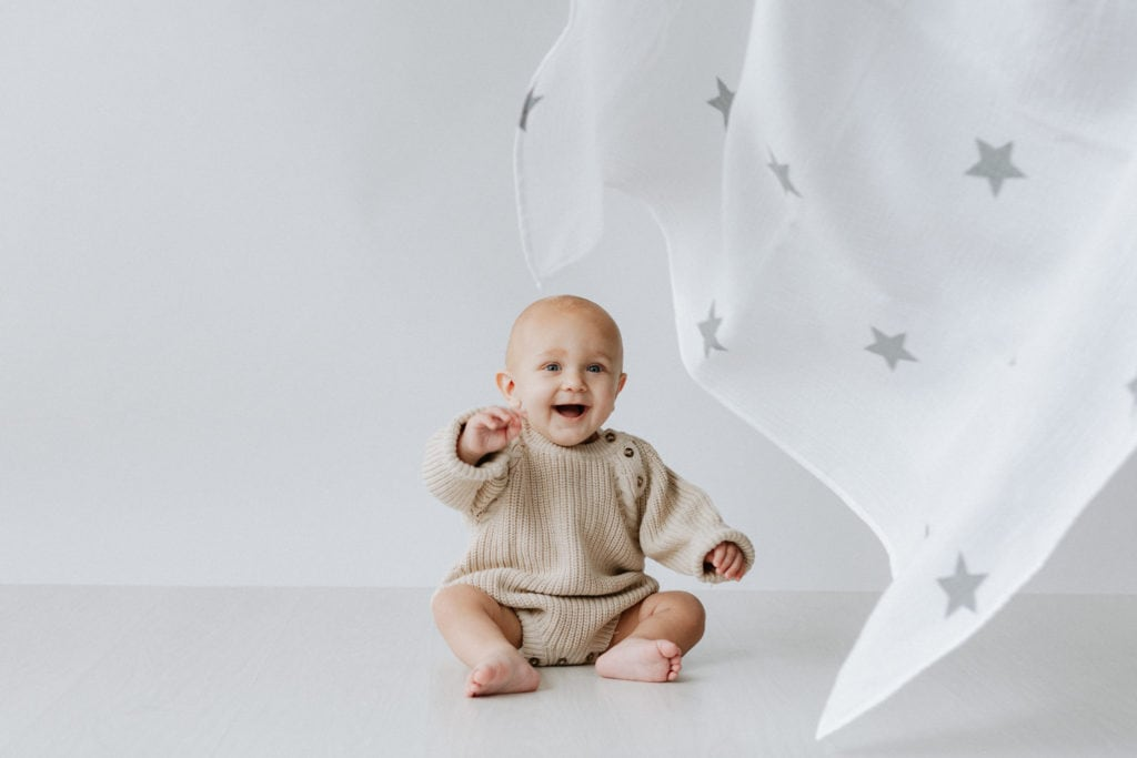 Baby boy wearing knitted romper smiling with star print muslin take at his Bexley baby photoshoot
