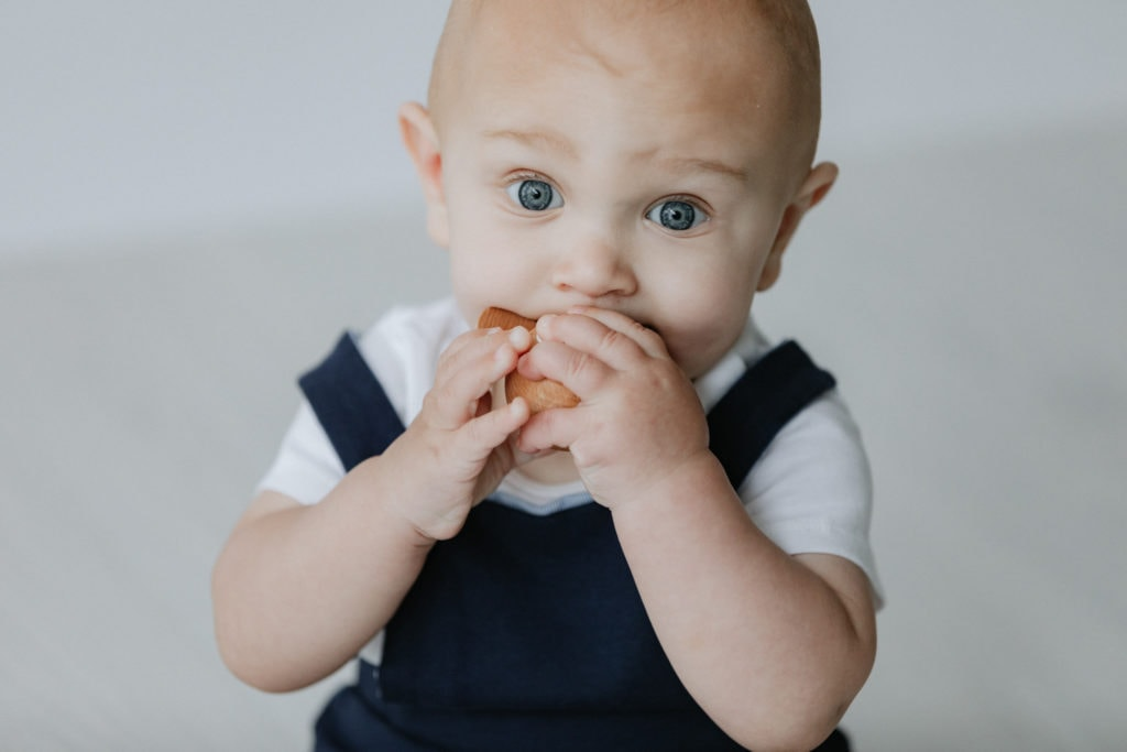Close up shot of baby with big blue eyes chewing a wooden toy at his Bexley baby photoshoot